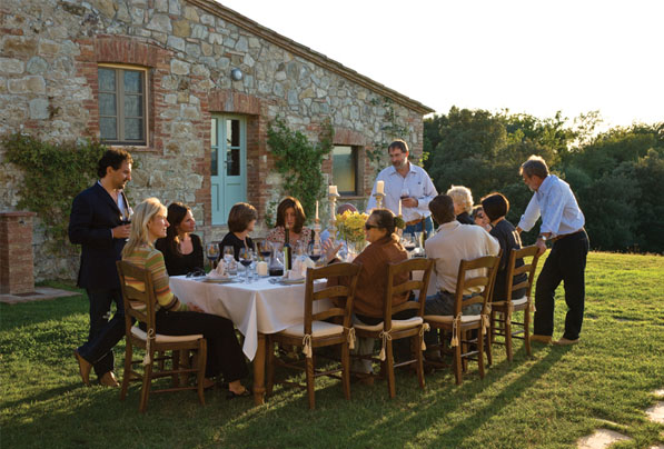 family and friends sitting down to dinner in Tuscany