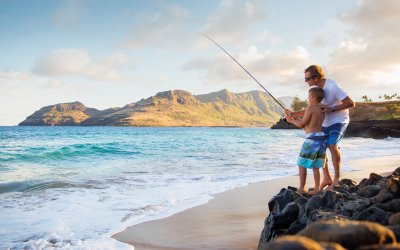 Father and son fishing off the beach