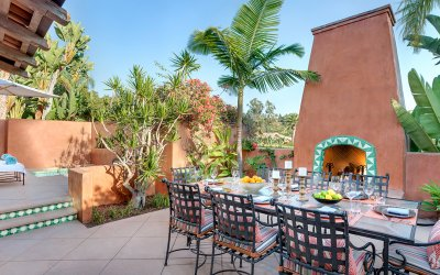 Villa patio with dining table and outdoor fireplace