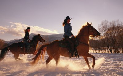 2 women riding horses in the snow