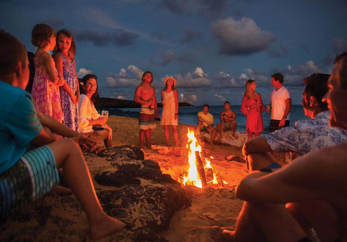 family and friends around beach campfire